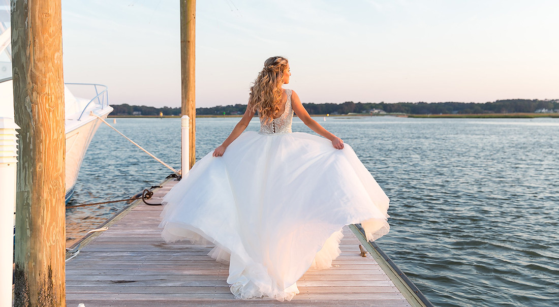 An Emily Weddings' bride's dress flows in the breeze on the dock in Virginia Beach