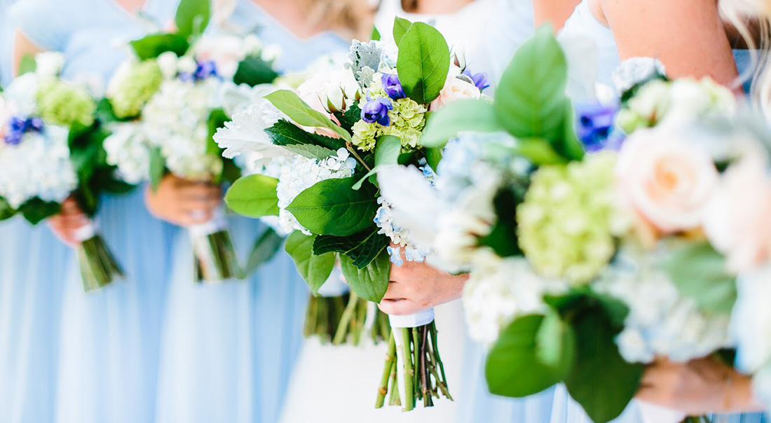 A close up shot of a bridal party's leafy green bouquets