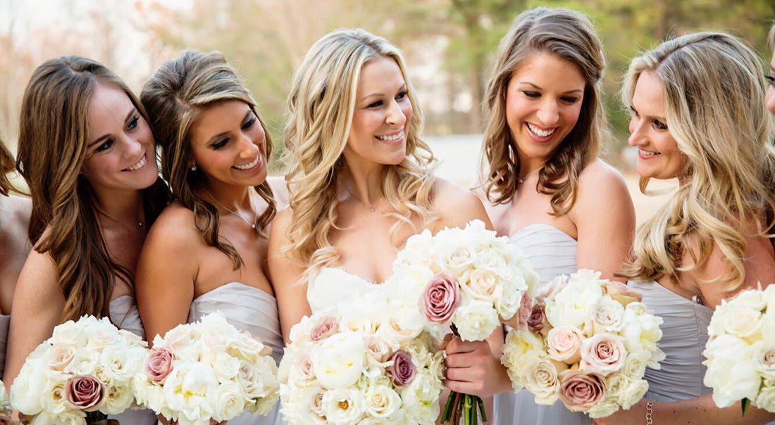 A bridal party giggles with their bouquets