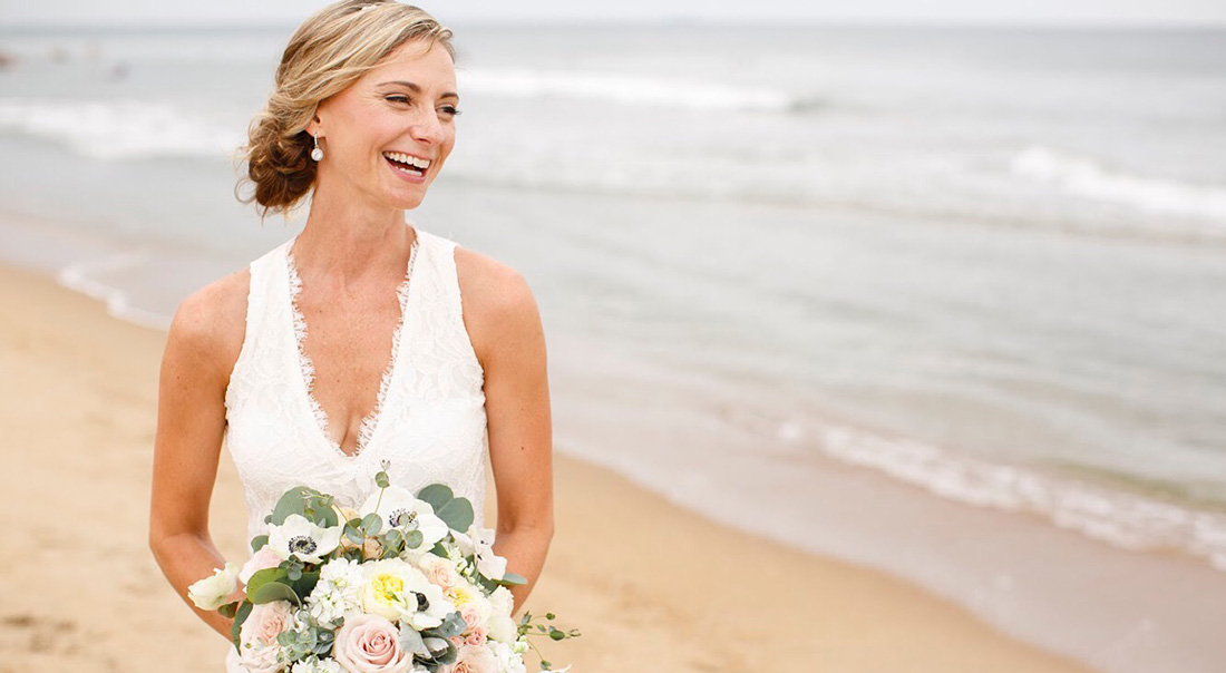 A beachy bride laughs in the surf