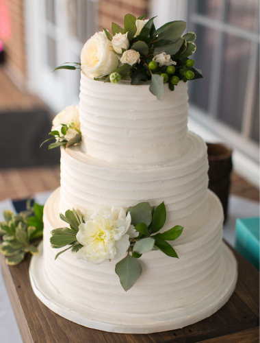 A white wedding cake decorated with white roses and greenery