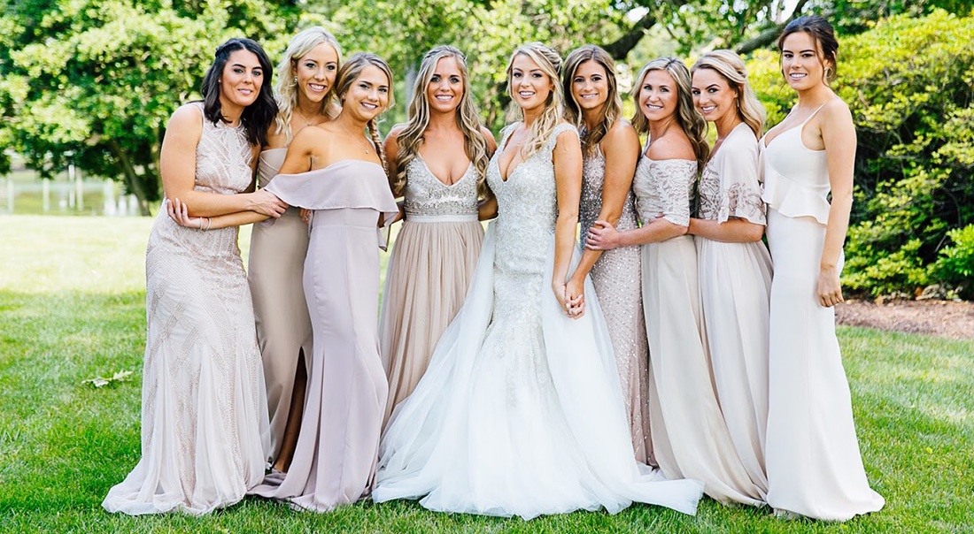 A bridal party holds each other close on the lawn